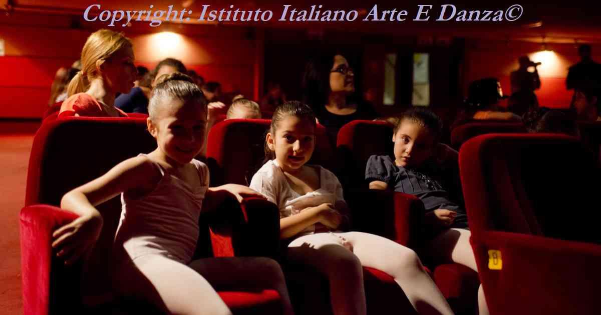 3 bimbe dei corsi di teatro si riposano in platea in attesa dell'inizio dello spettacolo
